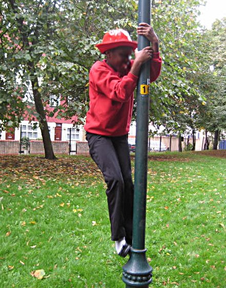 Yemisi climbing a lamppost